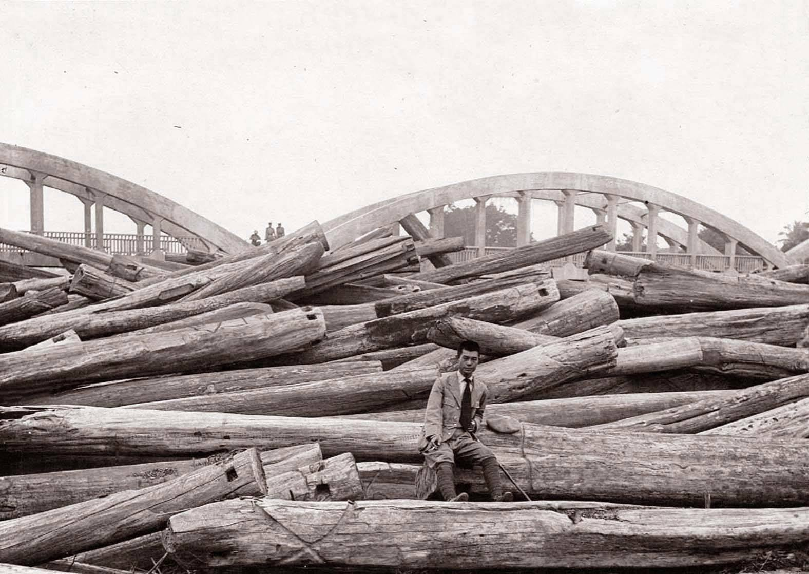 Unknown man on top of teak logs. Background Rachadapisek Bridge. ca. 1920. Picture Changton Natee.